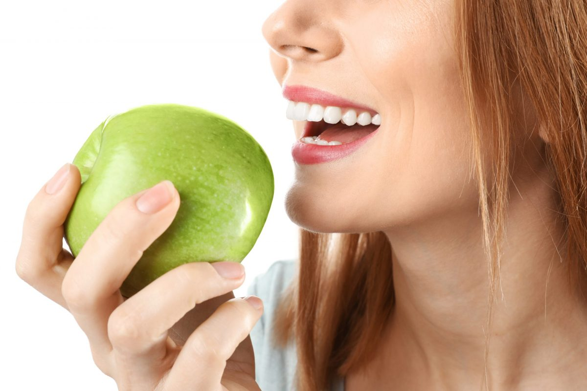 Close-up of a woman with white teeth eating a green apple
