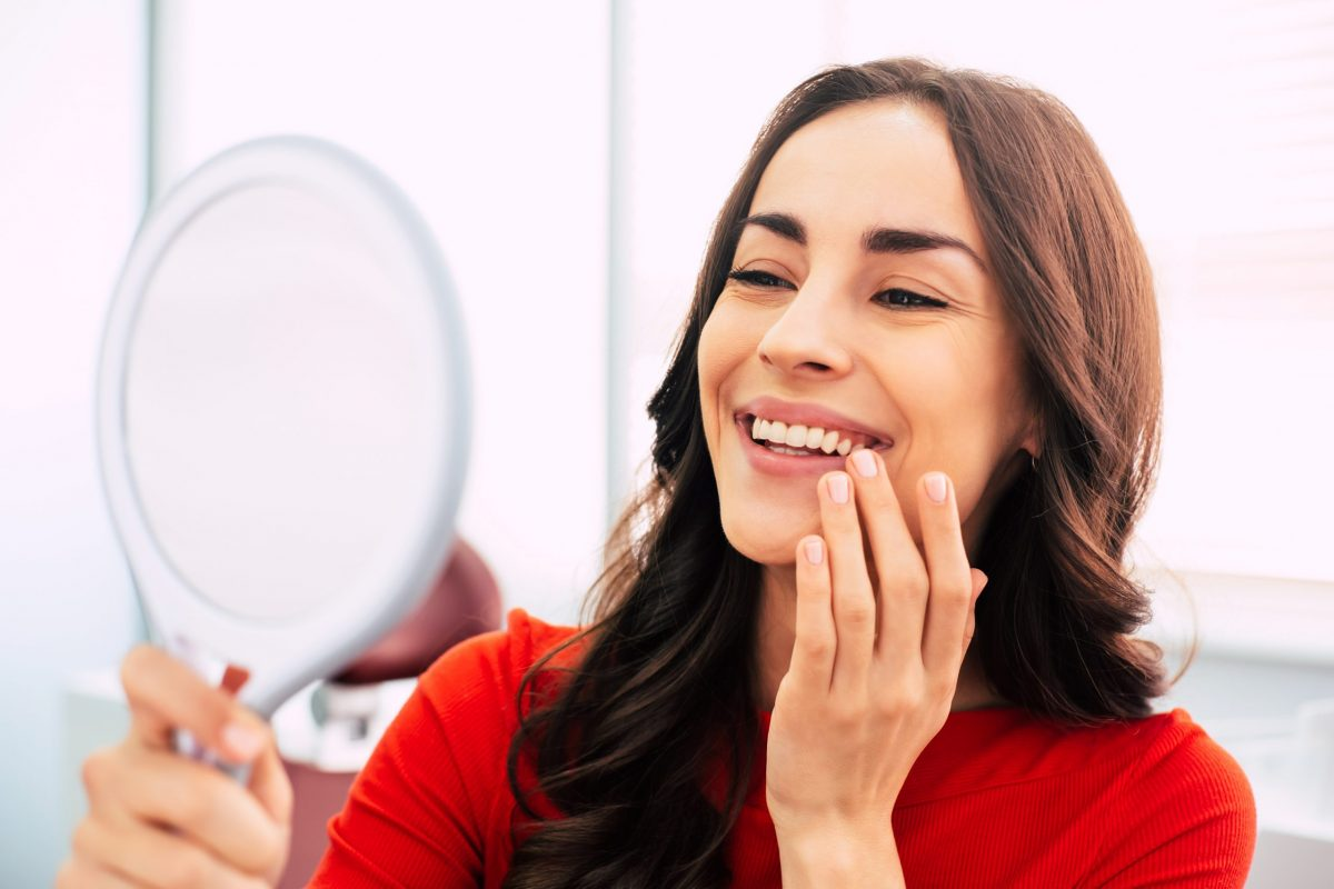 Woman use a mirror to look at her teeth