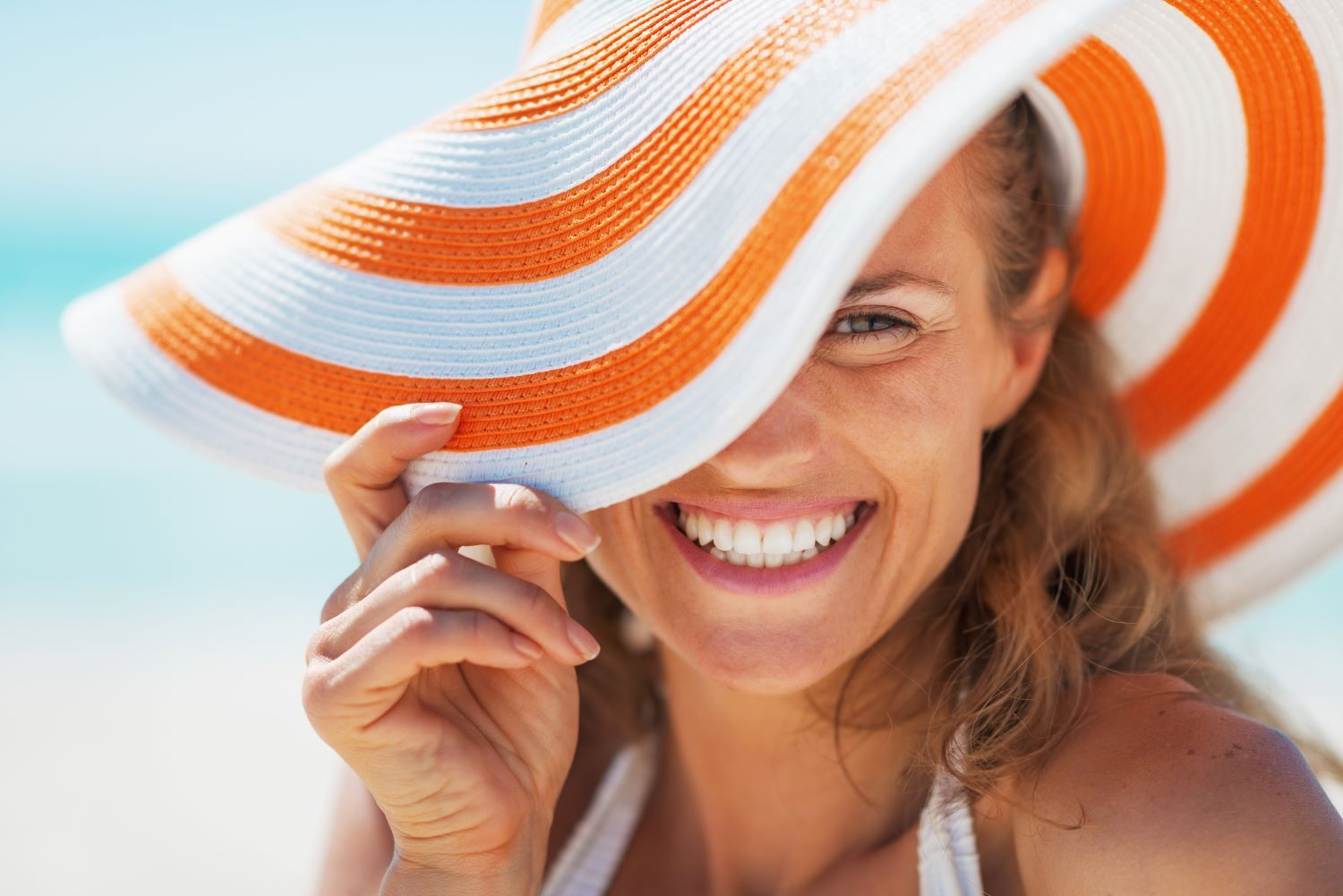 woman smiling on the beach with porcelain veneers